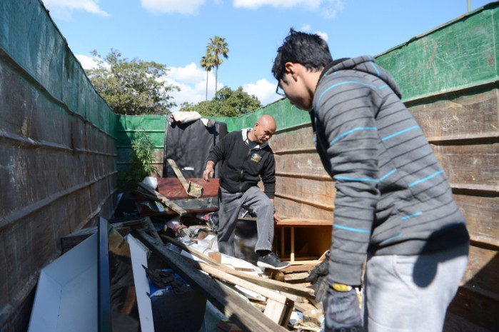 Sam Oun, and others begin using large dumpsters left along the flooded portion of Nordale Avenue in San Jose, Calif., on Friday, Feb. 24, 2017. Soon after this photo was taken, residents were asked to stop using the dumpsters until the area is no longer considered a hazardous danger. This area was hit hard by the recent flooding of Coyote Creek. Clean up efforts and efforts to restore services are well underway. (Dan Honda/Bay Area News Group)